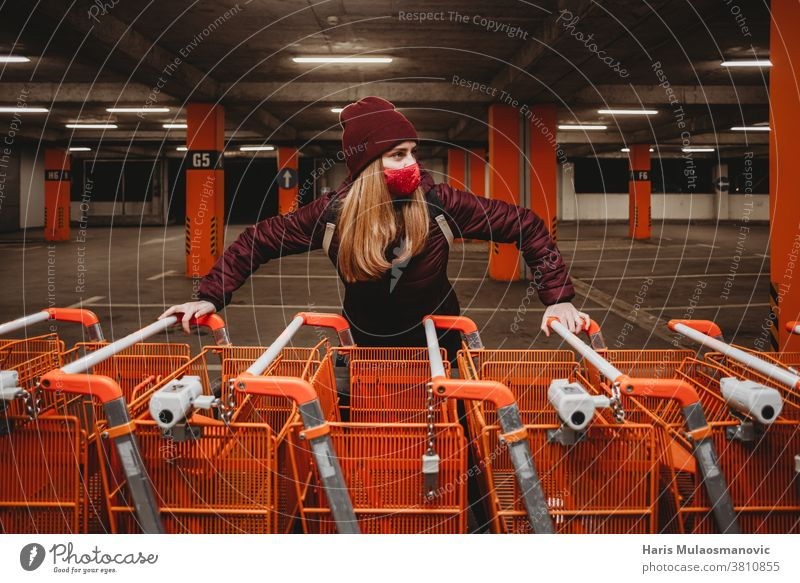 Woman with mask holding row of orange shopping carts in garage attractive bag beautiful big shopping carts car park caucasian city clothes cold collection