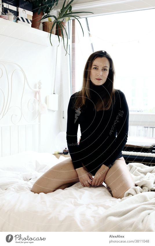 Close portrait of a young woman kneeling on a bed and looking into the camera Woman 18 - 30 years pretty fit Slim smart kind Pleasant Attractive Brunette