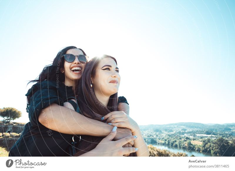 Two women having fun during a sunny day while smiling and hugging each other with copy space friendship joy female woman happiness young beautiful woman people