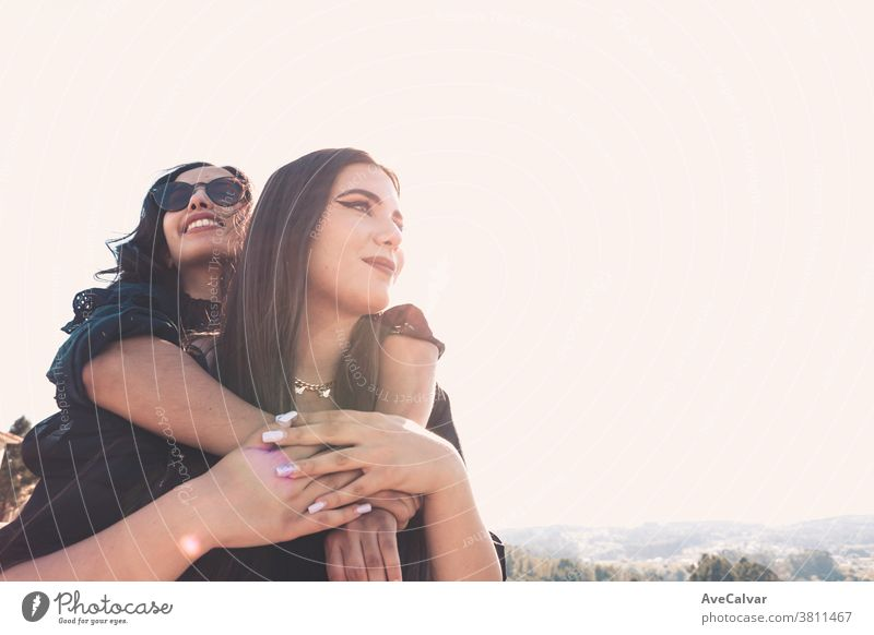 Couple of women having fun during a sunny day hugging each other with copy space friendship joy female woman happiness young beautiful woman people embracing