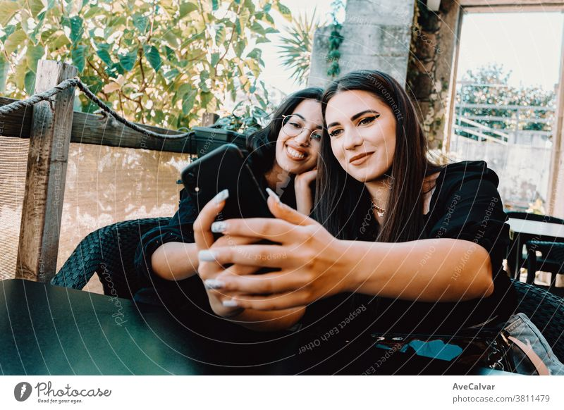 Couple of young women taking a selfie in a bar while smiling photo woman phone happy brunette friends joyful lady millennial outside smile stylish teenager two