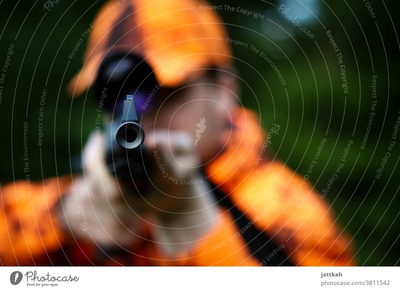View into the barrel of a hunting rifle held by a hunter dressed in orange. The focus is on the muzzle of the gun. Hunting Hunter Orange Weapon Rifle Shotgun