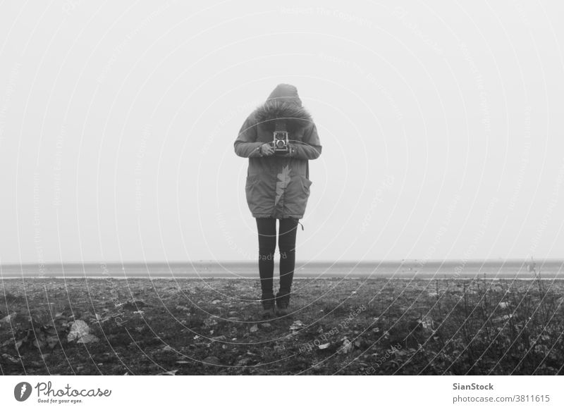 Woman with retro camera in a fog landscape misty black white b&w vintage winter art photo girl woman old taking person photographer holding photography outdoors