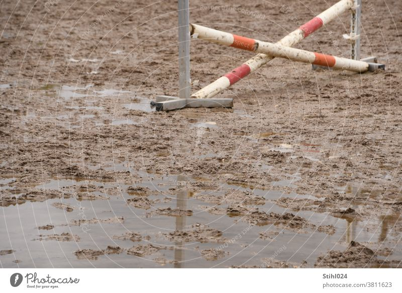 Equestrian sports ground with crossed obstacle sinks into mud with puddle equestrian sport Show jumping Horse Obstacle riding Ride slush Mud flooded Pillar