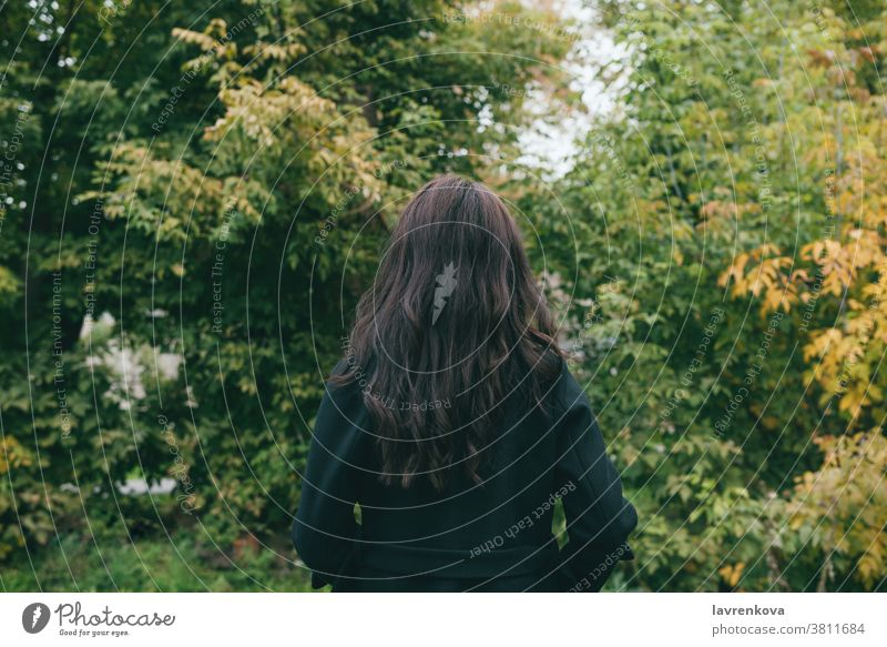 Portait from the back of female in dark coat outdoors in park or forest alone cold woman beautiful hair fall trees adult jacket autumn walking faceless