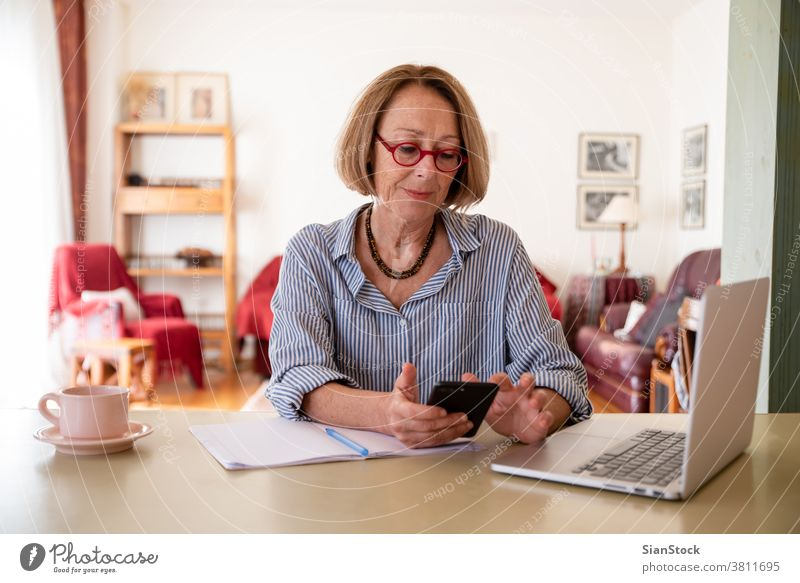 Middle age senior woman working at home using computer female laptop mature people one house phone smartphone message chat person lifestyle desk cheerful drink