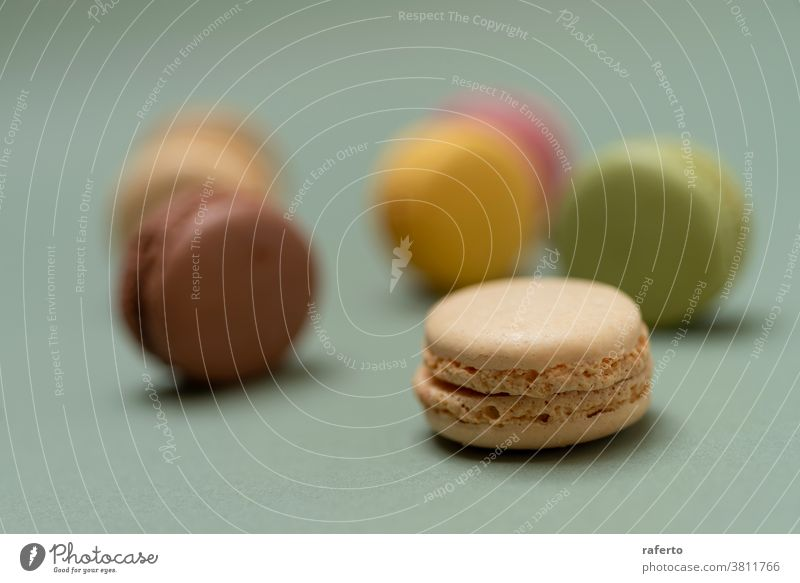 Colored tasty macaroons over a green background. In A Row Orange Purple Studio Shot appetizing arranged baked goods baking black background bright chewy color