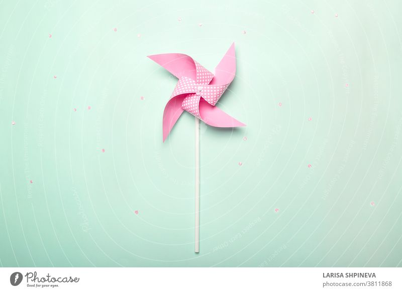 Pink paper spinner on blue background. Kids toy colorful pinwheel, carnival decoration on celebration party background. Top view, flat lay. childhood wind