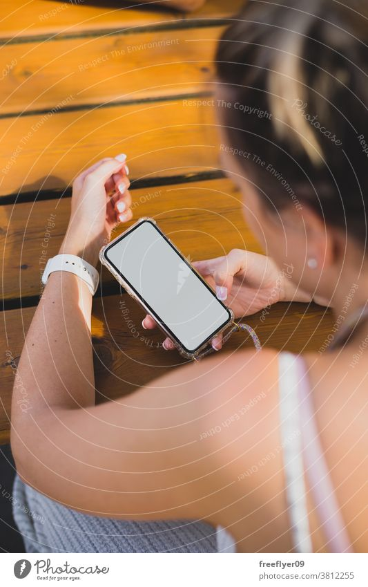 Mockup of a woman using her smartphone on a wood table mockup copy space blank mobile street maps resource media people white hand finger device showing app