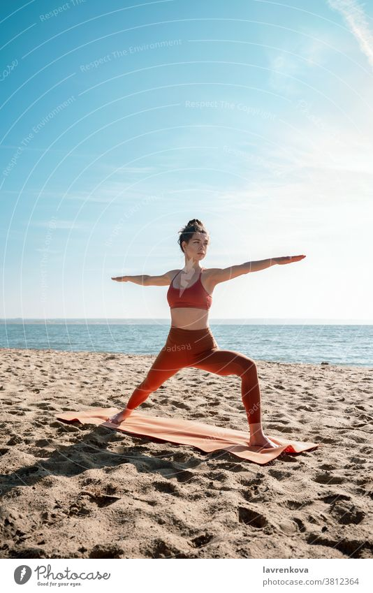 Young adult female practising yoga on a beach, Virabhadrasana II pose exercise training sea healthy athletic woman activity relaxation fitness lifestyle workout