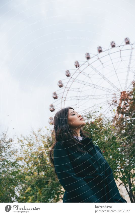 Young adult asian female in a dark coat in front of ferris wheel outdoors, selective focus woman autumn park casual leisure seasonal weekend young walkin fun