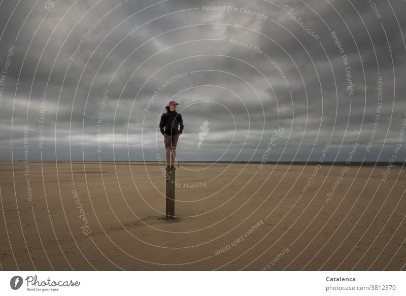 Promising, man standing on a pole on the beach on a cloudy day Beach Ocean coast North Sea Sky Horizon persons Sandy beach horizon Clouds Bad weather