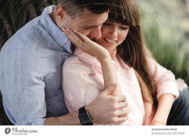 Image closeup of happy cheerful couple in summer clothes smiling and hugging while walking in the park. love story. They kiss and hug each other. selective focus