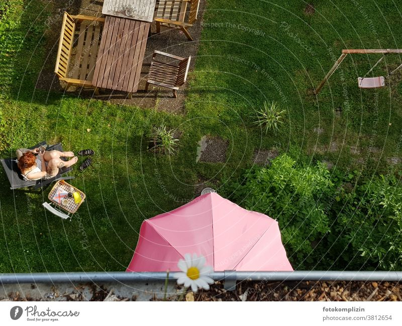 View from above into a garden with table, tray, chairs, swing, parasol and woman Garden Outdoor furniture Garden table Sunshade Swing Young woman Break chill