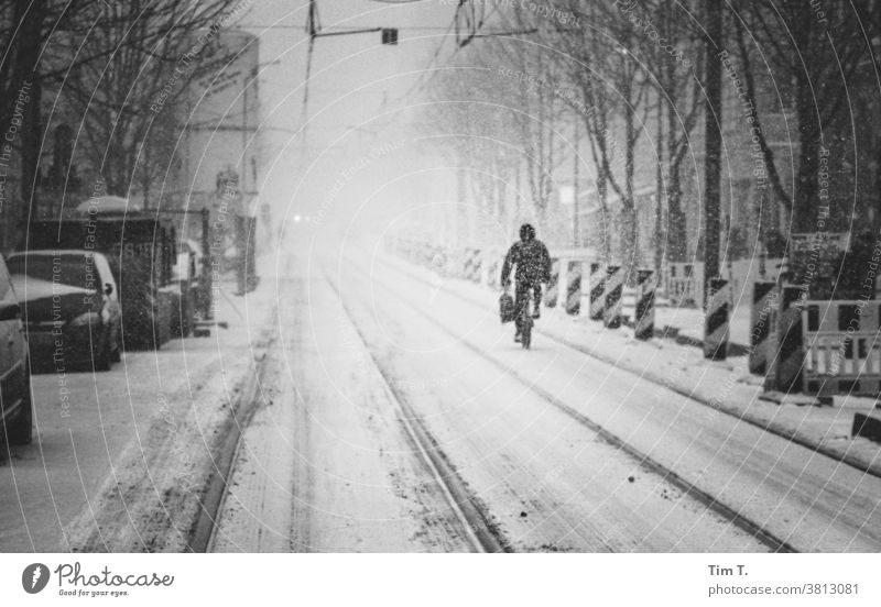 a snowy road with a cyclist in Berlin Prenzlauer Berg chestnut avenue Winter cyclists Exterior shot Downtown Town Day Old town Street Railroad tracks