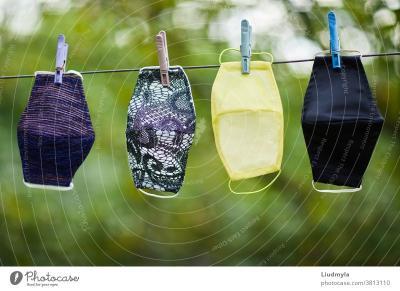 Coronavirus concept. Different types of handmade protective facial masks hanging on a rope outdoors air background care childish children clean clothes