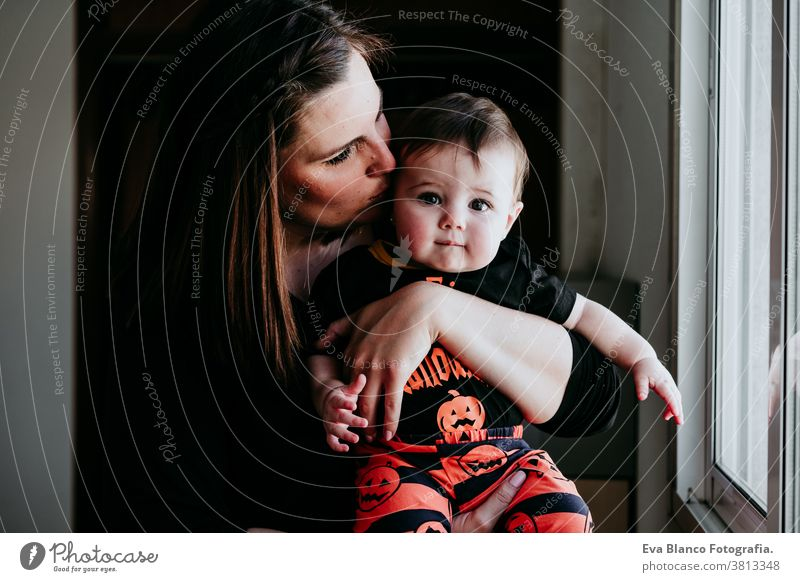 young mother and baby girl at home looking by the window. Baby girl wearing Halloween clothes. Family lifestyle indoors love together family childhood