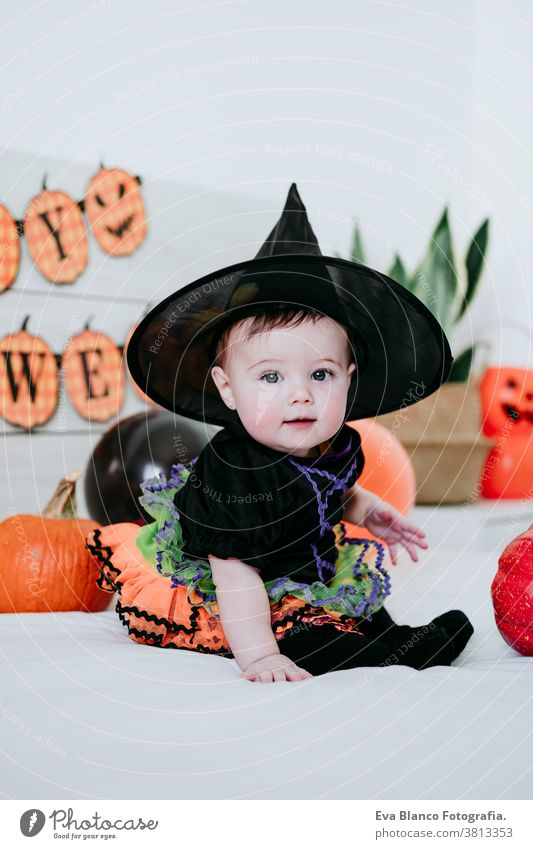 beautiful baby girl in witch halloween costume at home, sitting on bed with Halloween decoration, Lifestyle indoors trick or treat pumpkin balloons orange
