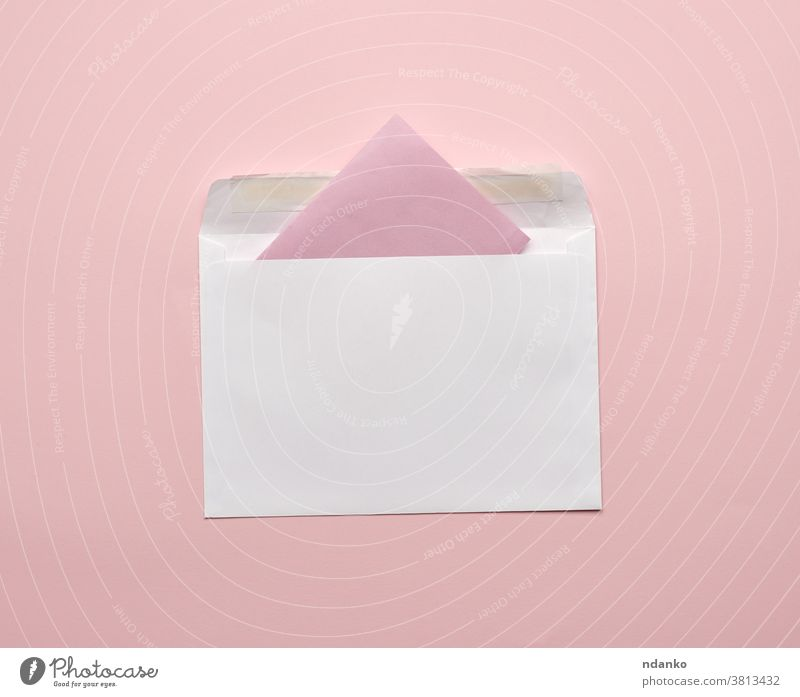 white envelope on a pink background empty information invitation letter mail message note open page paper postcard stationery studio template top blank closeup