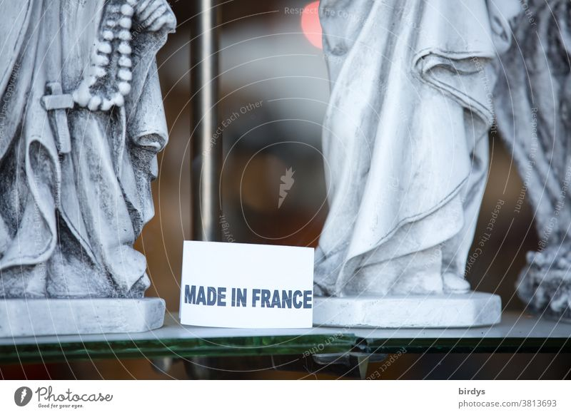 Made in France, sign in a shop window with Christian holy figures writing Shop window Figures of Saints Christianity Crucifix Belief Christian cross