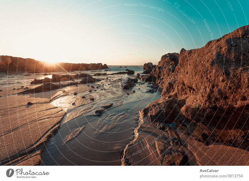 Colorful sunset on the beach over the rocks filled with mussels scene coastline nobody stone seascape panoramic nature outdoor travel view day seaside beautiful