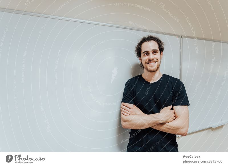 Young male teacher in front of a board smiling to camera copy space poster blank young man person banner isolated white display teenage fun point viewing