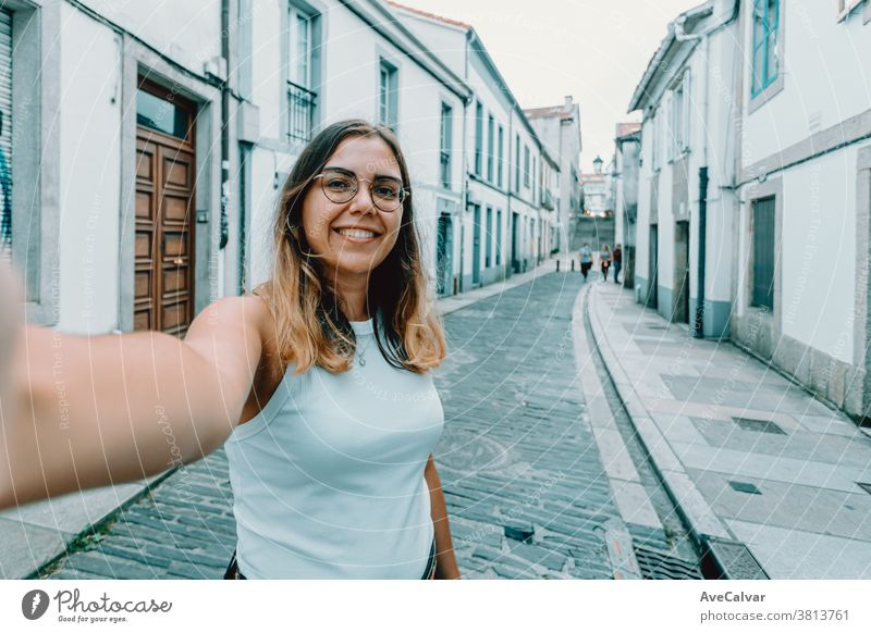 Young woman with glasses taking a selfie on a old spanish street pretty smart-phone trendy joyful brunette outdoors modern beauty style casual attire fun female