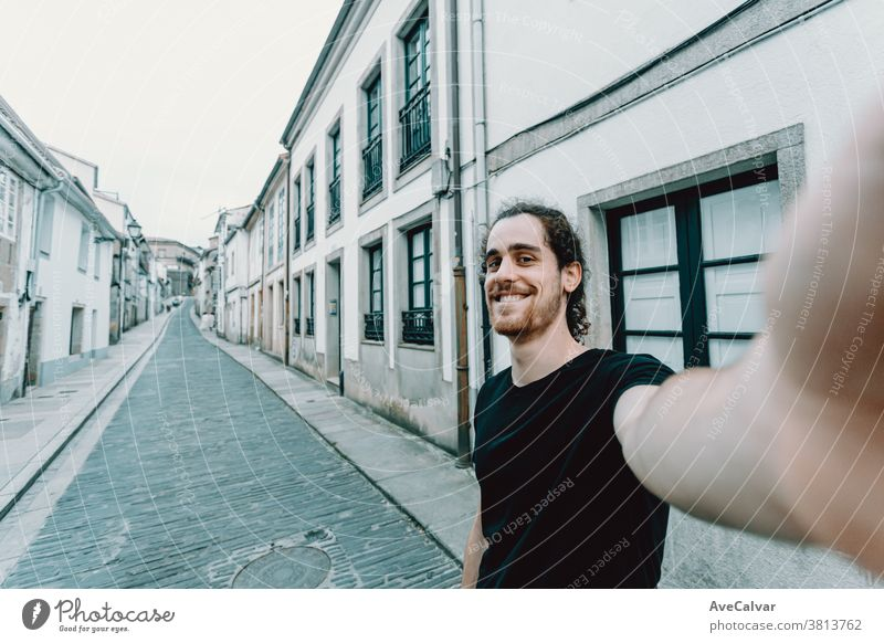 Young man with glasses taking a selfie on a old spanish street photo holiday maker modern bearded portrait cheerful happy waterfront backpack caucasian fun