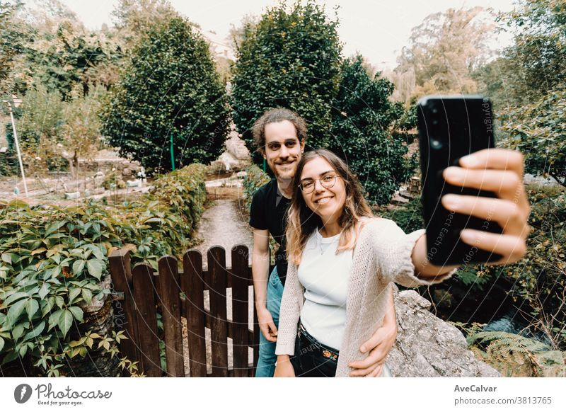Young and smiling couple taking a selfie in front of a beautiful rural house self-portrait fun smart-phone lifestyle summer together love male man smile park