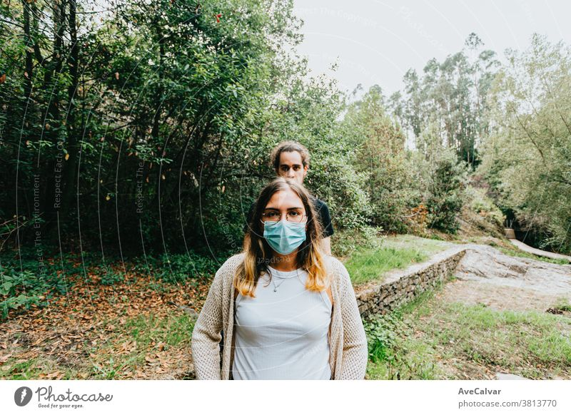 Front shot of a serious couple with the masks put on in the forest photo people mobile communication mobile phone park teenage happy selfie technology fun