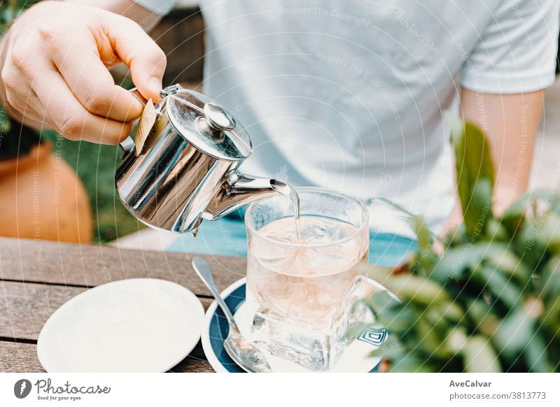 Young male serving an ice tea in a modern bar dry close herb man heat isolated health asia drink teacup breakfast hand pouring china white old hot beverage