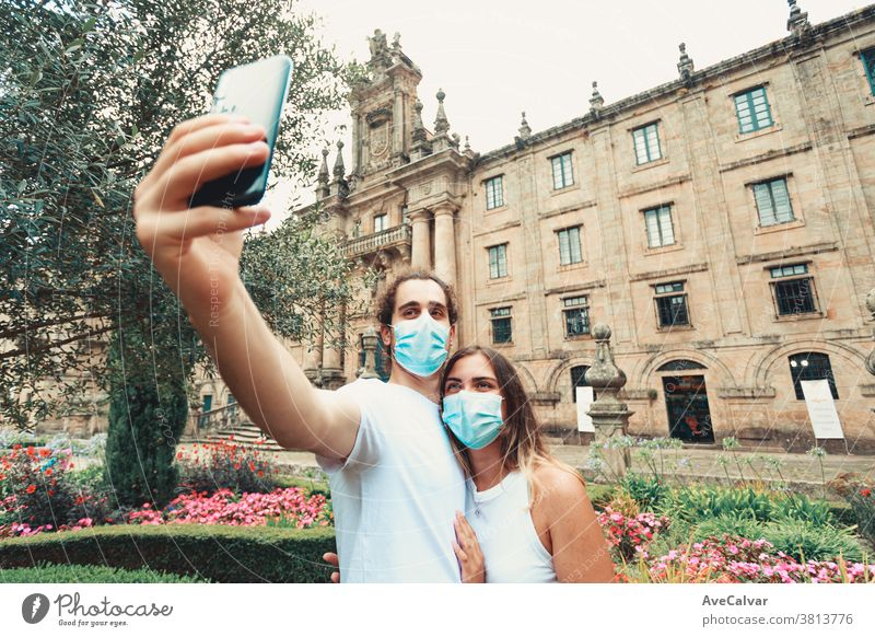 Young couple taking a fancy selfie with the masks on in a garden in front of an old building male virus man person family travel woman outbreak people