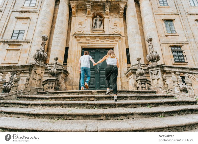 Young couple going up stairs while grabbing hands in an ancient building during a sunny day outside holiday maker man staircase outdoors people male boyfriend