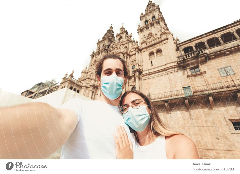 Young couple taking a selfie in a touristic place with the masks on together love young vacation boyfriend human relationships holiday friends happy travel