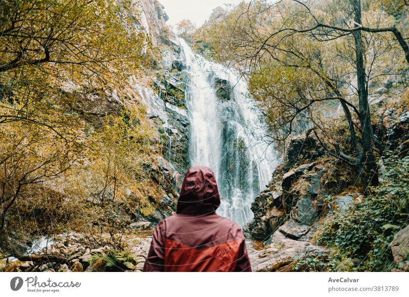 Woman out of focus in a purple oilskin standing in front of a giant waterfall backpack outdoors forest people looking view female white adventure sunny