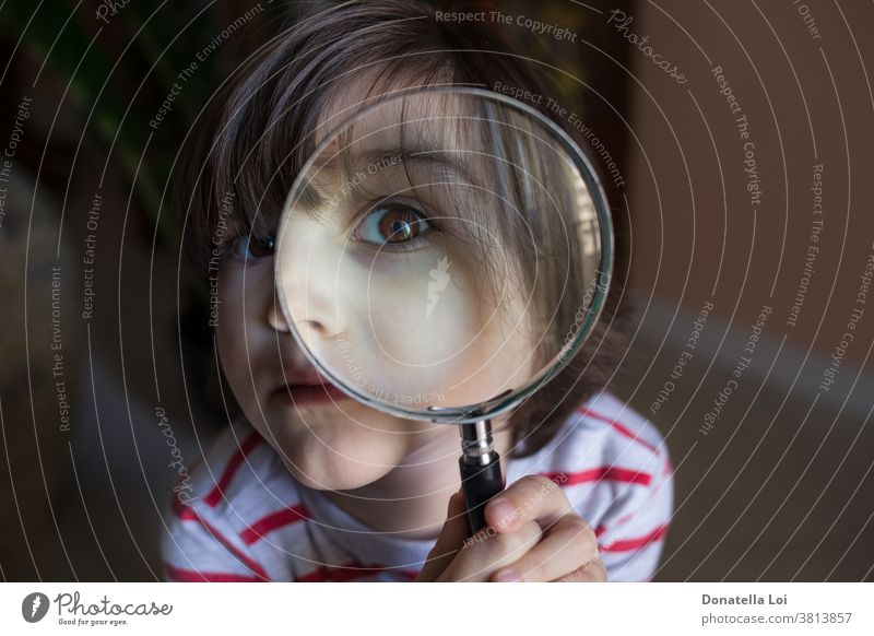 child with magnifying glass childhood close-up curiosity curious detective discovery education equipment experiment eyes eyesight face instrument kid learning