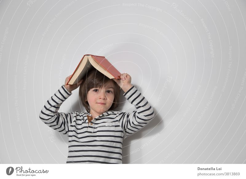 Child portrait with book on the head adorable boy caucasian cheerful child childhood cute day education emotion expression face fun happiness happy holding