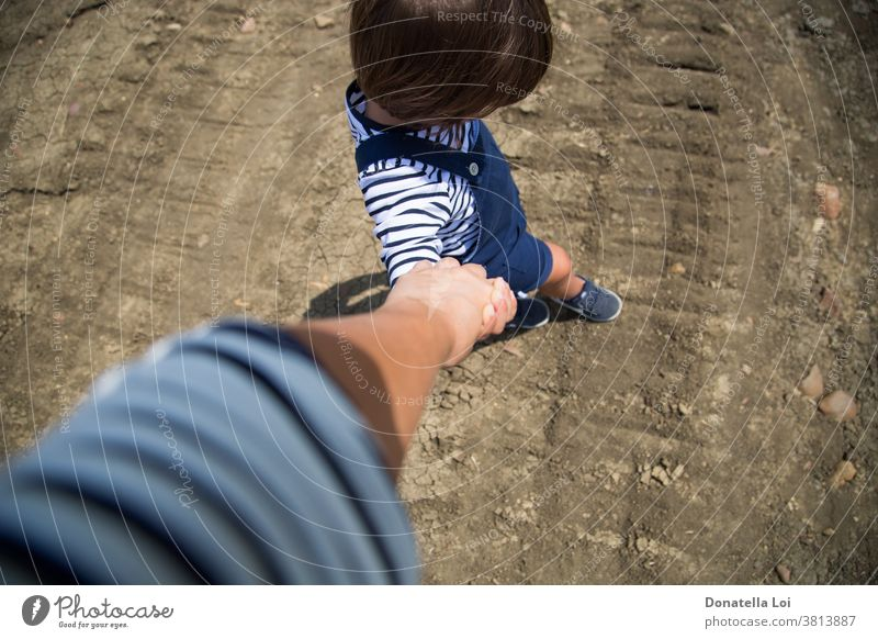 mother and son holding hands accompany casual childhood from above ground little boy stripes summer together walking