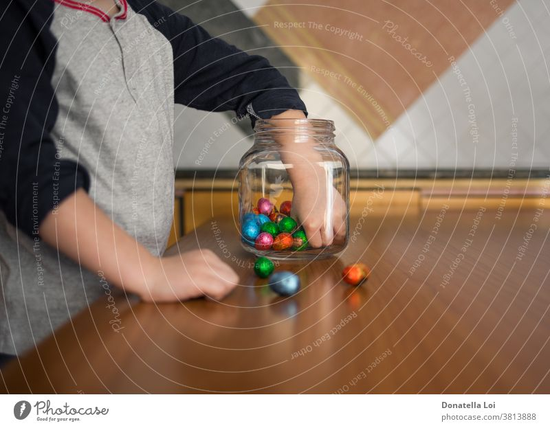 child takes chocolates from the jar at home celebration childhood colored concept craving easter eggs glass jar greed greedy greedy food hand hands kid kitchen