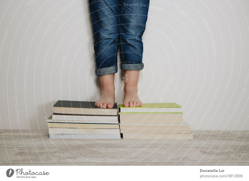 child standing on stacks of books barefoot casual dress caucasian childhood concept education educational feet fun grow home homework indoors isolated jeans kid