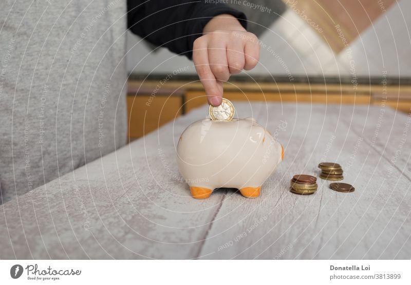 Child putting a coin into piggy bank at home banking budget cash caucasian ceramics child childhood coins concept crisis debt deposit earn economize economy