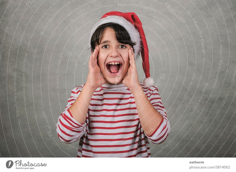 Merry Christmas, screaming kid wearing Santa Claus hat child christmas santa claus shout shouting christmas eve crazy excited announcement positive gesture