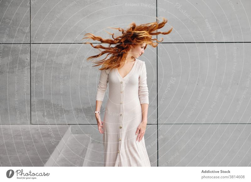 Ginger woman with flying hair standing near wall redhead ginger wind urban style long hair modern female red hair trendy color mystery contemporary elegant