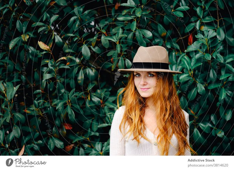 Young woman in hat standing in garden style redhead trendy red hair modern ginger vogue young female fashion long hair lady confident charming lifestyle elegant