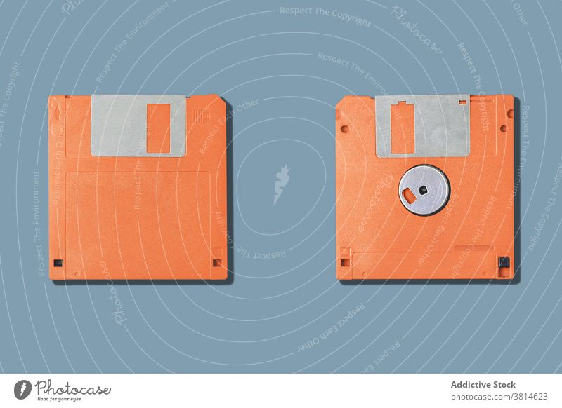 Computer floppy disks on gray background two old diskette computer pc old fashioned information data obsolete orange equipment device tool vintage retro