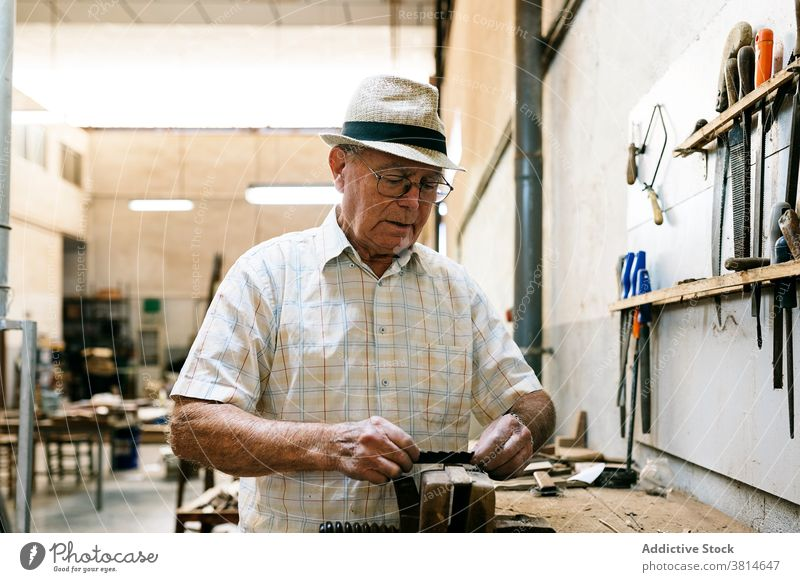 Senior male woodworker working in garage grind carpentry workshop man carpenter fold fan handmade wooden occupation skill tool messy artisan craft