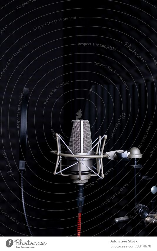 Modern microphone in dark studio record music soundproof foam equipment modern audio professional gadget song melody electronic device metal wire broadcast