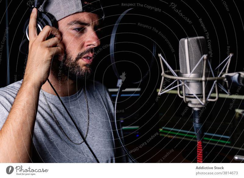 Man in recording studio microphone sing man artist hat singer headphones acoustic foam male sound proof song room music musician modern contemporary gadget cap