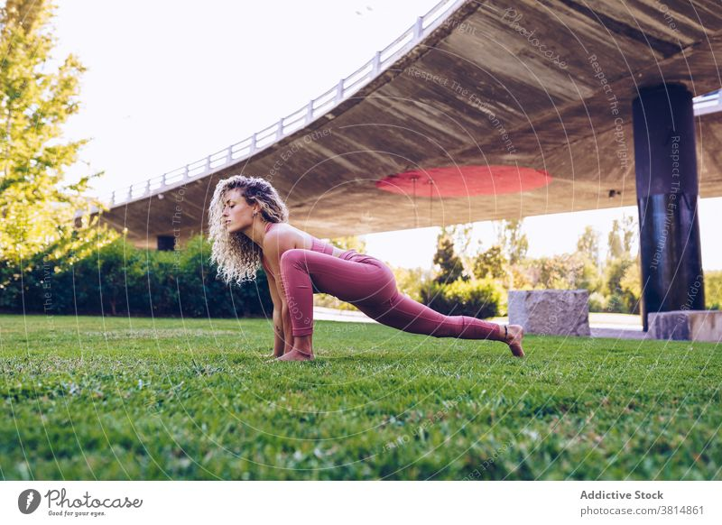 Focused woman practicing yoga in park asana flexible pose practice balance position slim female wellness harmony wellbeing activity concentrate vitality