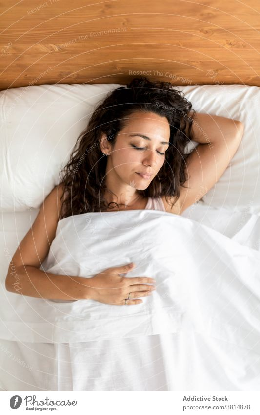Gentle woman sleeping in bedroom at home comfort soft pillow blanket calm dream female pajama lying cozy peaceful relax quiet eyes closed tranquil nap serene
